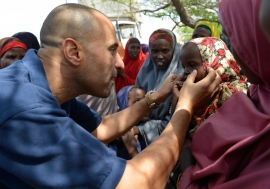 World Health Organization (WHO) official, Dr. Ahmed El Ganainy, checks the eyes of a little girl during a joint humanitarian assessment mission to Marka, Somalia, on 9 July 2014. UN Photo/David Mutua