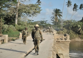 Ugandan soldiers serving with the African Union Mission in Somalia (AMISOM), walk across a bridge near the town of Janaale, Somalia.