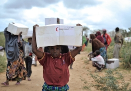 A young boy carries away a box of food from a distribution centre in Afgoye, Somalia. Photo: AU/UN/IST/Tobin Jones