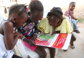 Girls in the city of Voinjama look at a poster that displays information and illustrations about how to prevent the spread of Ebola. Photo: UNICEF/2014/Liberia/Jallanzo