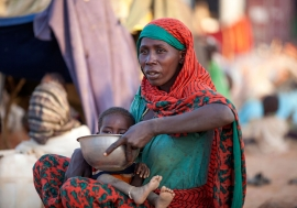 A displaced mother prepares food for her child outside the UNAMID base in Um Baru, North Darfur. UN Photo/Hamid Abdulsalam