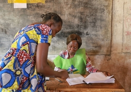 In Bangui on 14 February 2016, an electoral officer (right) assists a voter at a polling station for the Central African Republic's run-off presidential elections. A re-run of the 30 December 2015 legislative elections was also held. UN Photo/Nektarios Ma