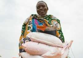 A woman carries sacks of seeds distributed to families in South Sudan during the COVID-19 pandemic.