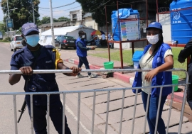 IOM staff stand ready to supervise COVID-19 preventive measures activities at a point of control in Kinshasa, Democratic Republic of the Congo.