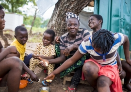 A refugee family from Cameroon sits outside their shelter at Adagom settlement in Ogoja province, south-east Nigeria. Photo Credits: Roqan Ojomo/ UNHCR
