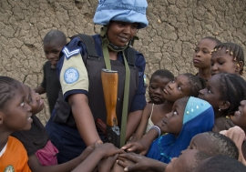 A Rwandan peacekeeper from the UN Multidimensional Integrated Stabilization Mission in Mali (MINUSMA) Formed Police Unit (FPU) speaks with children while patrolling the streets of Gao in northern Mali. Photo Credits: UN Photo/Marco Dormino