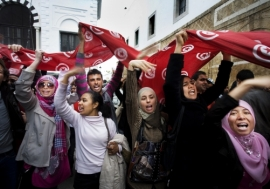 Agitating for change: Women wave flags during a demonstration in Kasbah Square, Tunis.     Photo: Panos / Alfredo D'Amato