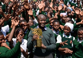 Teacher and Franciscan brother Peter Mokaya Tabichi, 36, holds his Global Teacher Award as he is cheered on by his students at Keriko Secondary School in Njoro, Nakuru county.            Getty Images/ Tony Karumba