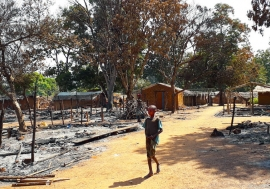 After armed clashes, a child walks among the charred ruins of Alindao, a city in the Central African Republic.
