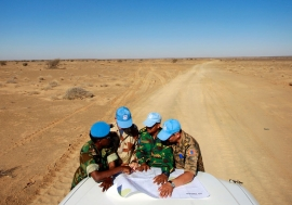 Peacekeepers with the UN Mission for the Referendum in Western Sahara (MINURSO) consult a map as they drive through vast desert areas in Smara, Western Sahara. Photo Credits:UN Photo/Martine Perret