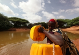 A woman drawing water from a man-made pond in drought-stricken Somali.  Photo: UNDP Somalia