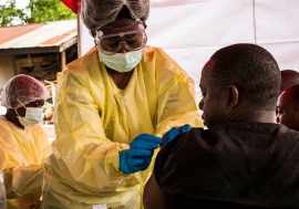 A health worker vaccinates a man against the Ebola virus in Beni