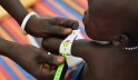 A health worker measures a baby girl's arm, at an outpatient therapeutic feeding centre at the Protection of Civilians site on the UN peacekeeping mission in South Sudan (UNMISS) base in Malakal, capital of Upper Nile State. Photo: UNICEF/Christine Nesbit