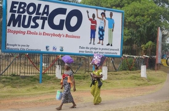 """Two women in Monrovia, Liberia, walk in front of a billboard, which says """"Ebola must go. Stopping Ebola is Everybody's Business."""" File Photo: UNMIL/Emmanuel Tobey"""