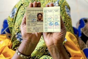 A coffee farmer from Musasa, Rwanda, shows her health insurance card. Panos/Andrew Esiebo