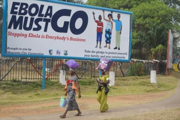 "Two women in Monrovia, Liberia, walk in front of a billboard, which says ""Ebola must go. Stopping Ebola is Everybody's Business."" File Photo: UNMIL/Emmanuel Tobey"