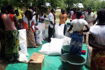 People gather at Mikolongo school in Chikwawa district, Malawi, to receive rations of maize, pulses, oil and fortified corn soya blend from WFP to prevent malnutrition.