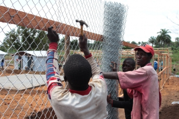 Workers build an enclosure at the Mayagba Ebola community care centre construction site in Bombali District, which is among the areas worst affected by the disease in Sierra Leone. Photo: UNICEF/John James