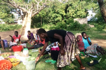 Eunice Achieng Omondi, a survivor of violence hands checks on the vegetables she is taking to the market during a meeting with members of Usoma Support Group for Survivors of Violence in Kisumu. Picture Jane Godia
