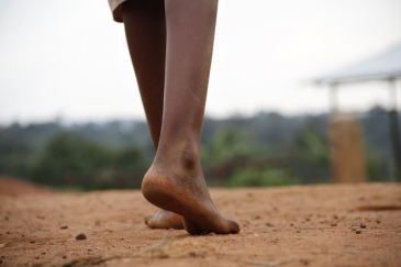 On 29 May, Centia, 12, walks barefoot across dusty ground in Kirundo Province, Burundi. Photo credit: UNICEF/UNI186074/Nijimbere