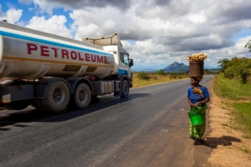 A Tanzanian woman walks to the market as a petrol lorry passes by. Photo: Alamy /Wietse Michiels Travel Stock