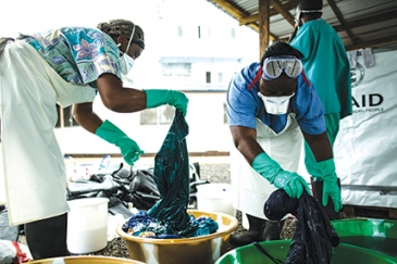 Health workers clean hospital scrubs and protective gear at the Island Clinic for Ebola treatment centre in Monrovia, Liberia, during the 2014 Ebola outbreak.   USAID/Morgana Wingard