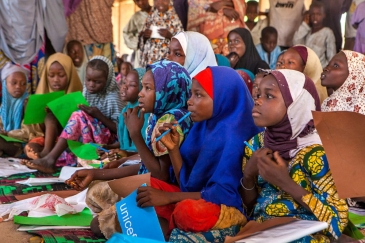 Girls use their new school supplies during a class in an informal learning centre in a UNICEF-supported safe space for children in the Dalori camp for internally displaced people, in the north-eastern city of Maiduguri in Borno State. Photo: UNICEF/UNI193
