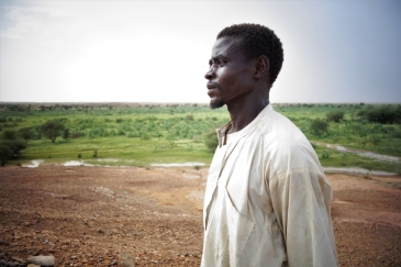 Boyi, 26, stares off into the distance over the 30 hectares of land that he now shares with other 29 community members. Photo: IOM/Monica Chiriac