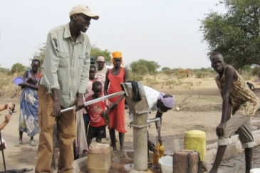 Salva Dut (left) pumps water from one of the boreholes he has helped drill in South Sudan. Photo: Water for South Sudan