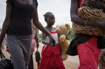 A young refugee and her family cross the border between South Sudan and Uganda. Photo: UNHCR/Will Swanson