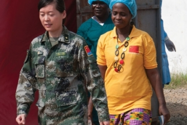 Beatrice Yardolo, right, Liberia's last Ebola patient, walks out of the Chinese Ebola Treatment Unit (ETU) in Monrovia, Liberia, at the beginning of a short ceremony celebrating her survival and release from the ETU on March 5. Photo: UNMEER/Simon Ruf