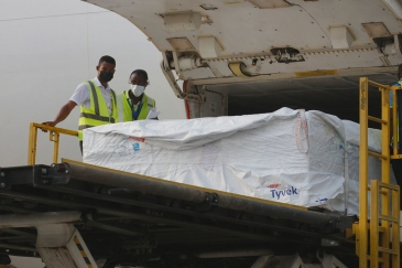 Staff unload the first shipment of COVID-19 vaccines distributed by COVAX at Kotoka International Ai