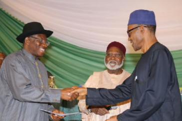 Former Nigerian President Goodluck Jonathan (left) and President-elect Muhammadu Buhari shake hands. In the middle is former head of state, Gen (Rtd) Abdulsalam Abubakar.