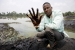 Claimant Eric Dooh shows the crude oil that has damaged the banks of the creek through his village in Ogoniland, Nigeria.