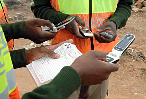 Non-governmental peace workers sharing information by cell phone to help monitor