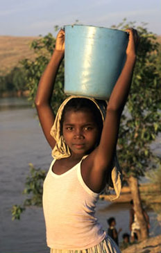 Girl fetching water from a river in Madagascar