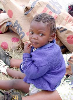 """Child sitting amidst sacks of relief grain in Lesotho: Emergency aid is vital, but """"just shipping in food is not enough,"""" says UN Secretary-General Kofi Annan: Poverty and other causes of famine must also be addressed.  Photograph: WFP / R. Lee"""