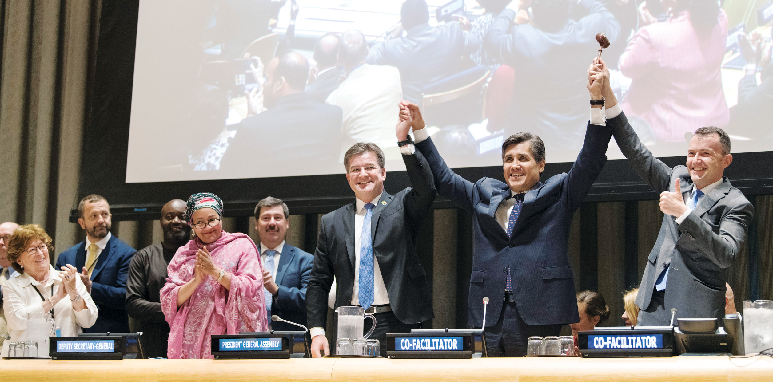Miroslav Lajčák (centre), President of the 72nd session of the General Assembly, and Co-facilitators for the United Nations Global Compact on Migration process, Juan José Gómez Camacho (second from right), Permanent Representative of Mexico to the United Nations, and Jürg Lauber (right), Permanent Representative of Switzerland to the United Nations, hold up the gavel at the end of the meeting finalizing the draft document.