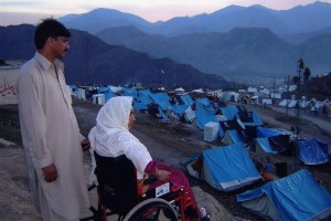 Image of a refugee camp showing a man and a woman in a wheelchair looking at the camp in the sunset