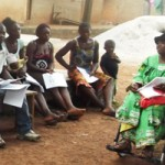 Image of village discussion led by a woman with a disability