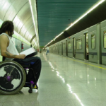 A man in a wheelchair sits at a train platform