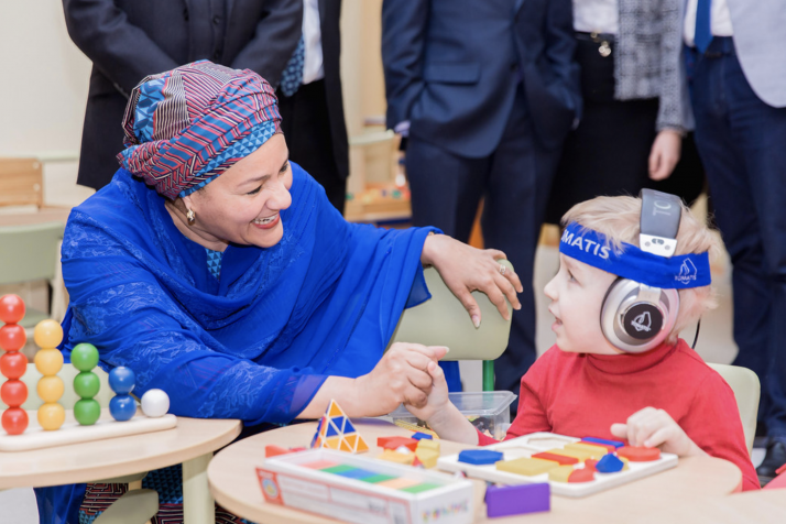 Deputy Secretary-General Amina Mohammed visits the Republican Rehabilitation Center for Disabled Children, on her first day in Minsk, Belarus. In this photo she talks to a small boy using a hearing device.