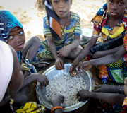 Children eating from a bowl of rice