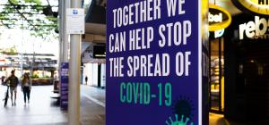 "A sign in a public area reads ""Together, we can help stop the spread of COVID-19."""