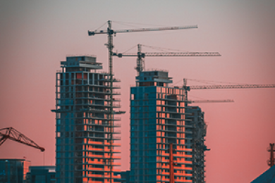 Cranes build three skyscrapers at sunset