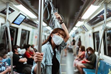 Woman in mask looks at camera while standing and holding a pole on a train