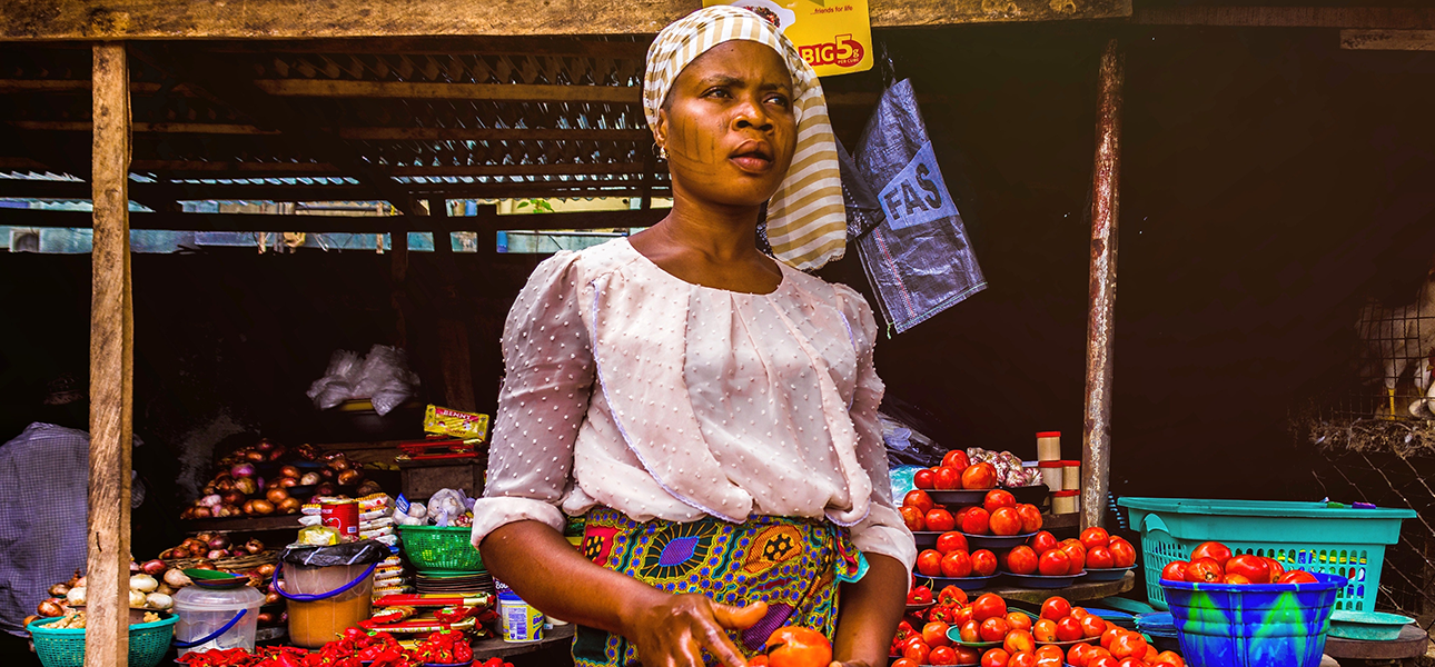 Woman holds tomatoes for sale at an open air market, looking up into the distance.