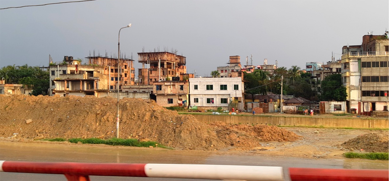Buildings under construction next to a river in Bangladesh