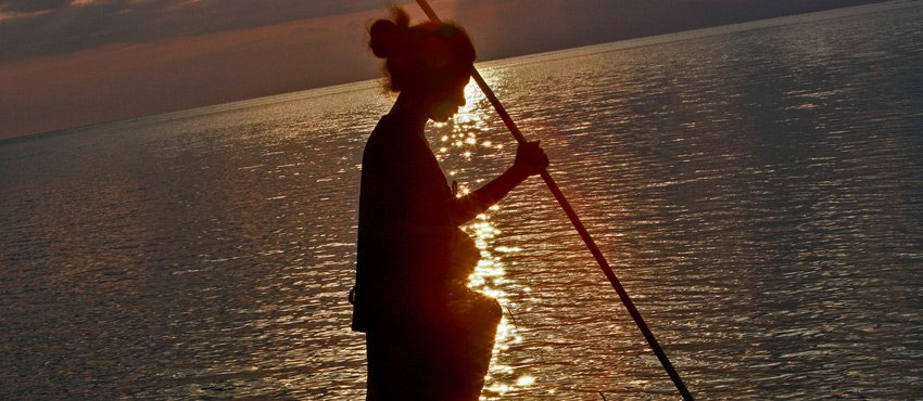 Photo of Timorese woman fishing at sunset