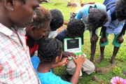 Group of kids looking at an island photo in an electronic tablet device